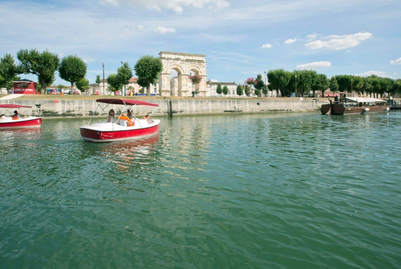 Petit bateau sur la Charente, devant l'arc de germanicus, Saintes